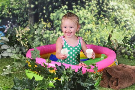 2 year old: An adorable 2 year old delighetedly playing outside in her kiddie pool. Stock Photo
