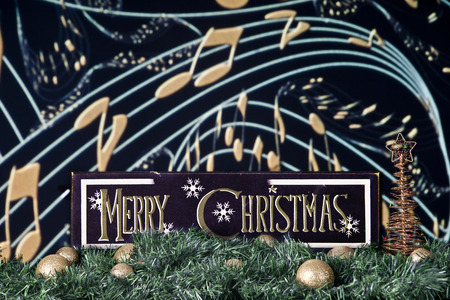 musical staff: A black and gold Merry Christmas sign on a bed of garland and gold bulbs against a backdrop of musical staff and notes.