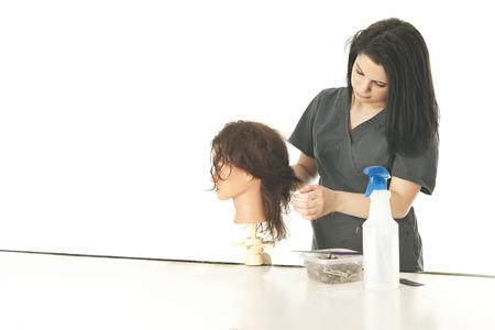 mannequin: Une jolie jeune étudiant en cosmétologie les cheveux de sa pratique mannequin comme elle commence à coiffer. Sur un fond blanc avec un espace sur la gauche pour votre texte. Banque d'images