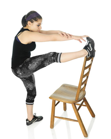 girl working out: An attractive teen girl working out with one foot on the top of a ladderback chair while stretching to touch her toes.  On a white background.