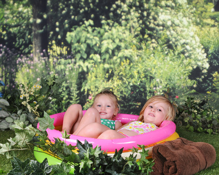 kiddie: Two preschool sisters looking at the viewer as they relax outside in their filled and inflated kiddie pool.
