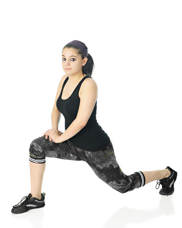 lunges: A pretty teen girl looking at the viewer as she lunges in her workout outfit.  On a white background. Stock Photo