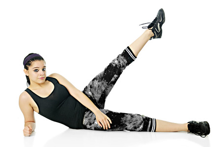 looking at viewer: A pretty teen girl looking at the viewer as she performs side-lying leg lifts in her exercise outfit.  On a white background. Stock Photo