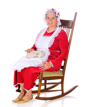 mrs santa: Mrs. Santa Clau petting a sleeping kitten while rocking in her chair.  Isolated on white. Stock Photo