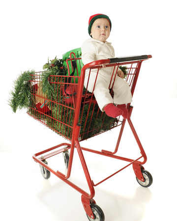 decore: An adorable baby boy riding in the childs seat of a red shopping cart filled with Christmas gifts and decore.  On a white background.