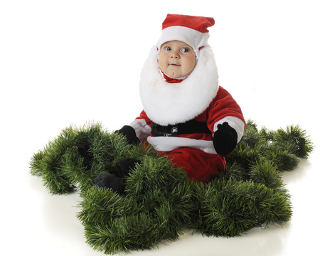 baby in suit: An aodrable baby Santa sitting happily surrounded by green garland.  On a white background.
