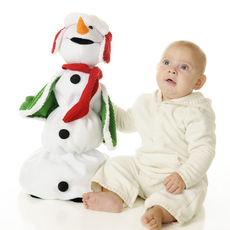 An adorable baby boy happily sitting with his toy Christmas snowman.  On a white background. photo