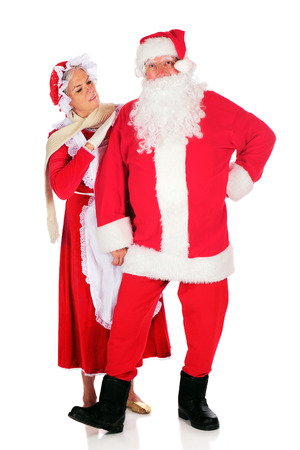 Mrs. Santa inspecting her husband before he takes off on his midnight flight.  On a white background. Imagens
