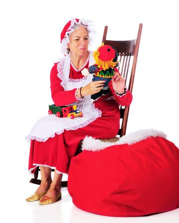 señora: Señora Claus tirando juguetes de bolsa de Santa Claus para inspeccionar o admirarlos. Sobre un fondo blanco. Foto de archivo