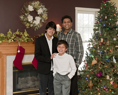 A father with his elementary and young teen sons in the family living room decorated for Christmas. photo