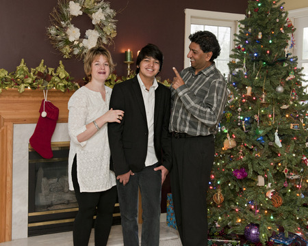 A family of 3 standing in their Christmas-decorated living room.  The dad is teasingly warning his young teen son while the boy and wife pose for a portrait. photo