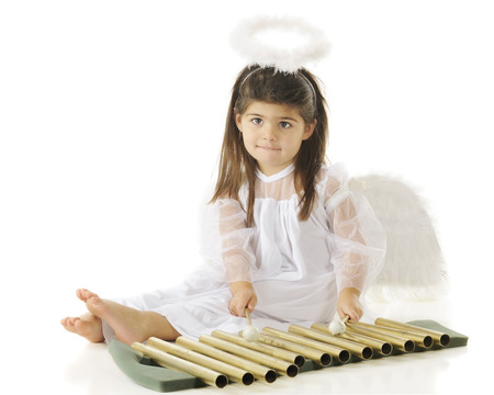 chimes: An adorable preschool angel practicing her xylophone-style chimes.  On a white background.
