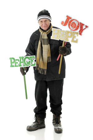 bundled: A bundled senior man happily preparing to place cheerful yard signs for Christmas.  On a white background. Stock Photo