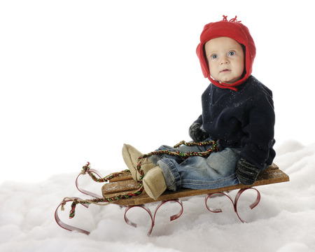 baby sit: An adorable baby boy sitting on a sled in the snow, looking up questioningly.  On a white background. Stock Photo
