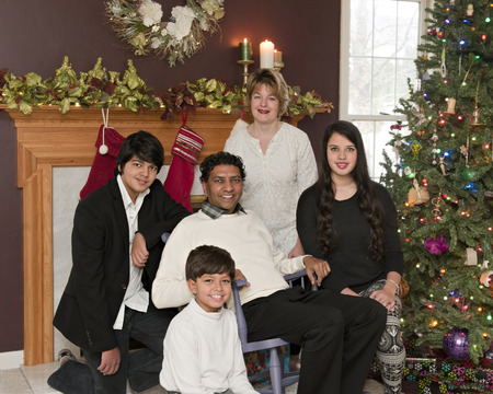 A biracial family of five happily in their Christmas-decorated living room. photo