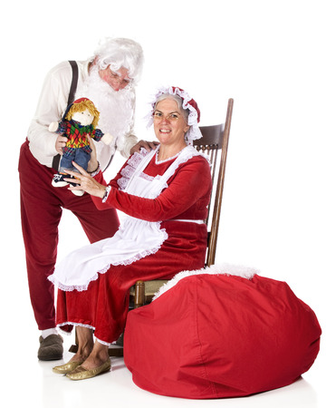 work clothes: Santa in his work clothes showing his wife the doll he just made while she proudly shows it off for the viewer to see.  On a white background.