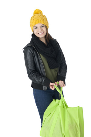 cloth cap: A pretty teen girl in yellow ski cap and black leather jacket happily carrying a cloth shopping bag.  On a white background.