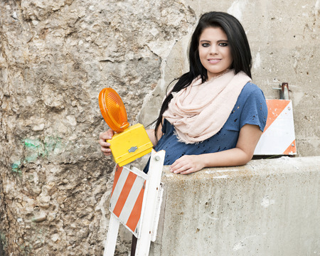 leaning by barrier: A pretty geen girlholding a caution light while  standing behind orange and white striped and  concrete barriers.   Space on the concrete barrier and crumbling wall behind her for your text.