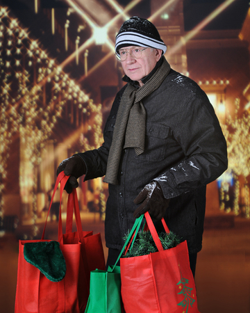 adorning: Image of a senior adult man carryng full shopping bags outside in front of Christmas lights adorning the exterior of a shopping mall. Stock Photo