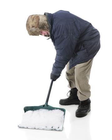bundled: Full length image of a bundled senior man scooping up a shovelful of snow.  On a white background. Stock Photo