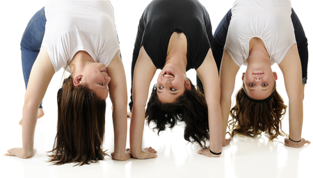 tween: Three tween girls making side-by-side gymnastic bridges.  Two are talking and laughing together, the other looks straight at the viewer.  On a white background. Stock Photo