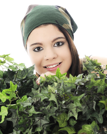 head scarf: Close-up of a beautiful teen girl in a camouflage head scarf peeking over thick, green ivy.  On a white background. Stock Photo