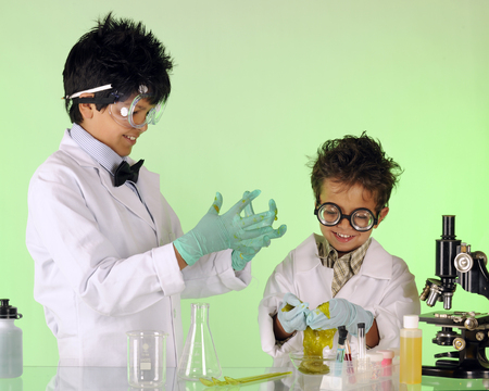 happy asian man: A preteen having fun with his preschool brother in a chemistry lab, both working as mad scientists.