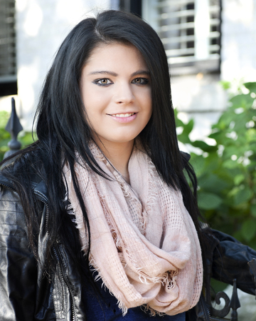 Close-up of a beautiful, black-haired teen stading in her scarf and leather jacket by the wrought iron gate of her home.