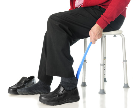 operative: Close-up view of a senior man sliding into his loafers with the aid of a long-handled shoe horn.  On a white background. Stock Photo
