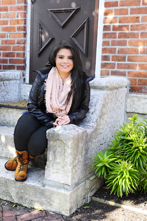 stoop: A beautiful teen girl happily sitting on her front stoop in the shade on a sunny day.