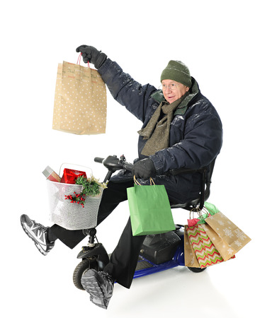 bundled: A bundled senior man on a scooter loaded with Christmas gifts.  Hes delightedly holding up the largest of the gift bags.  On a white background.