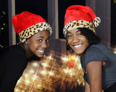 pretty people: A preteen and teenage sister delightedly smiling at the viewer wearing Santa hats by a Christmas light decorated window.