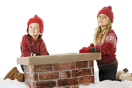 kindergartner: A young boy and girl looking for Santa by the chimney on a snow-covered roof.  On a white background.