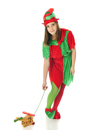 greeen: A pretty teen elf looking up at the viewer as she tests a pull-toy helicopter.  On a white background. Stock Photo