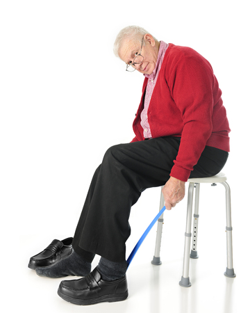 post operative: Full length view of senior adult looking at the viewer as he puts his loafers on with a long-handled shoe horn.  On a white background.