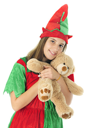 looking at viewer: A pretty teen elf looking at the viewer as she happily hugs a tan teddy bear ready for Christmas giving.  On a white background.