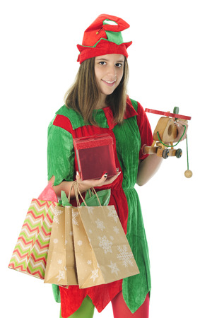 gift bags: A pretty teen elf smiling at the viewer as she carries gift bags, a wrapped box and a toy helicopter in preparation for Christmas.  On a white background.