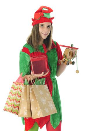 pull toy: Una bonita adolescente duende sonr�e al espectador mientras se lleva bolsas de regalo, una caja envuelta y un helic�ptero de juguete en la preparaci�n para la Navidad. Sobre un fondo blanco.