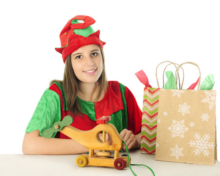 gift bags: A pretty teen elf smiling at the viewer from behind a table with a toy wooden helicopter and two gift bags.  On a white background.