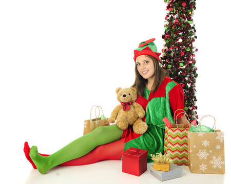 panty hose: A pretty teen Christmas elf looking at the viewer as she happily relaxes among Santas gifts.  On a white background with space on the left for your text.
