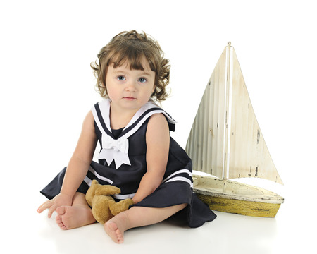 looking at viewer: A beautiful barefoot baby looking at the viewer in her sailor dress, a toy sail boat behind her.  On a white background.
