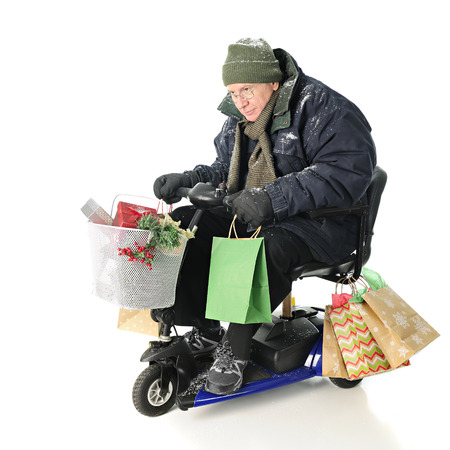 intensely: A bundled senior man intensely driving his Christmas gift-laden scooter.  On a white background.