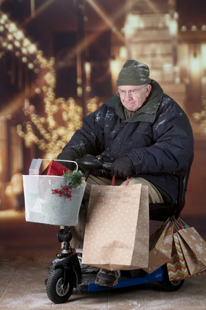 A intense senior man outside  leaving a mall decorated in lights.  Hes driving a scooter filled with gift bags and boxes. Stock Photo