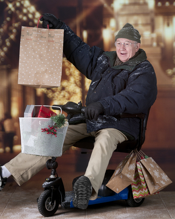 christmas shopper: A senior Christmas shopper delighted with his purchase as he drives his scooter away from a light decorated mall.