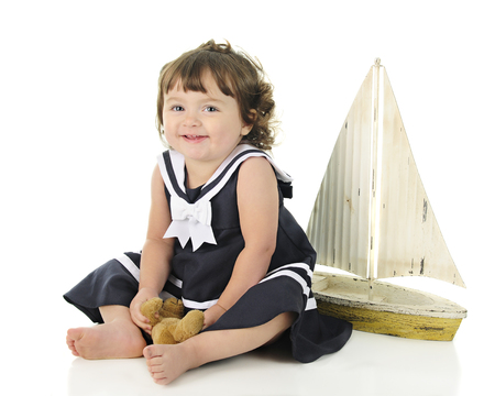 sailor girl: An adorable baby sailor girl happily sitting with her toy sailboat behind her.  On a white background.