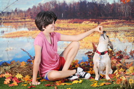 rewarding: A attractive young teen rewarding her dog with a treat as they play on a warm fall day by the edge of a pond.
