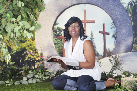 sandal tree: An attractive mature woman looking up from reading her Bible.  She sits outside on the grass in front of a large donut-shaped stone through which 3 wooden crosses are visible.