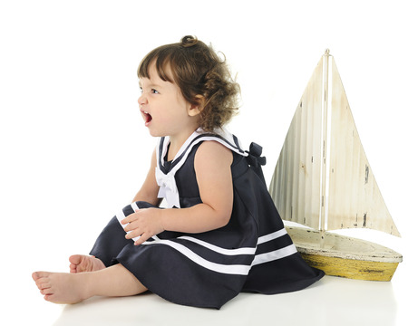 baby isolated: Profile of an adorable little girl angrily growing while sitting barefoot in her sailor dress. Stock Photo