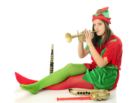An attractive teen elf tlooking at the viewer as she tests toy instruments for Santa.  On a white background with space on upper left for your message. Stok Fotoğraf