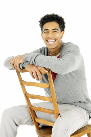 backwards: A happy young man sitting backwards on an old, ladder back chair.
